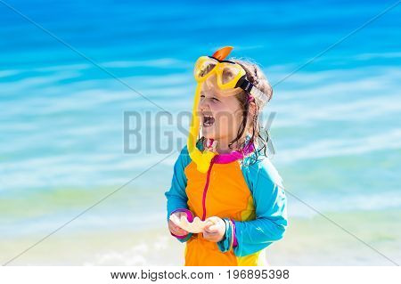 Happy little girl snorkeling on exotic beach during family summer vacation. Kid with snorkel gear and sea shell at ocean shore on coral island. Child swimming and diving in tropical water.