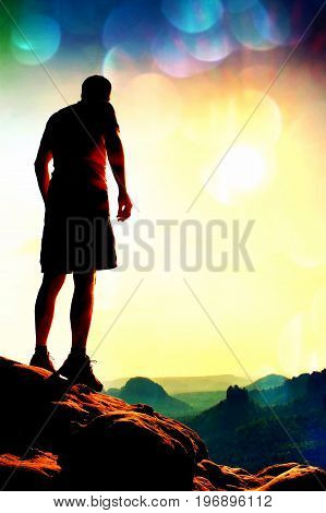 Film Grain. Slim Tourist In Pants On The Cliff Of Rock Empire Is Watching Down To Morning Valley. Ho