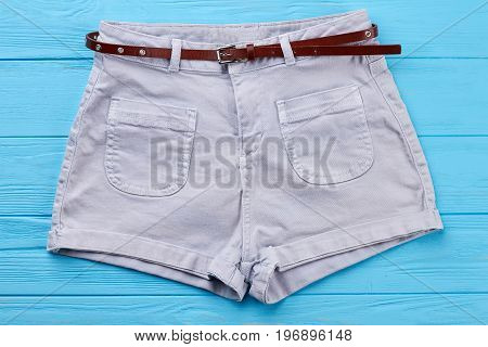 Modern cotton shorts with belt. Comfortable female summer short pants, blue background.