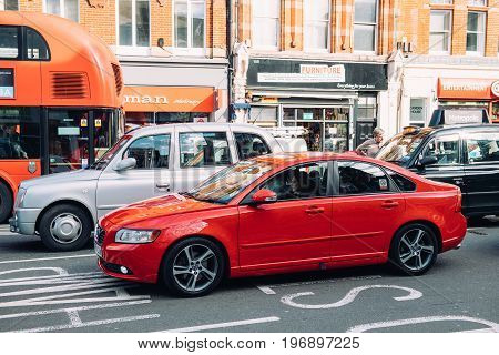 LONDON UNITED KINGDOM - MAR 9 2017: Clean red Volvo limousine next to Hackney Carriage taxi car and other uber cars driving slow in a traffic jam in London United Kingdom