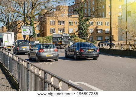 LONDON UNITED KINGDOM - MAR 9 2017: Luxury Mercedes-Benz car next to VW Golf and Hackney Carriage taxi car and other uber cars driving slow in a traffic jam in London United Kingdom