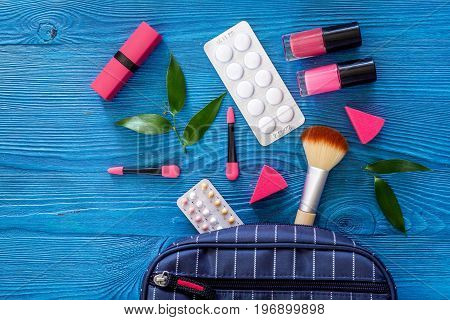 Cosmetic bag with contraceptives and pills on blue table background top view.