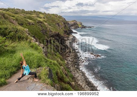 a woman practicing yoga on the rugged and scenic coast of Maui