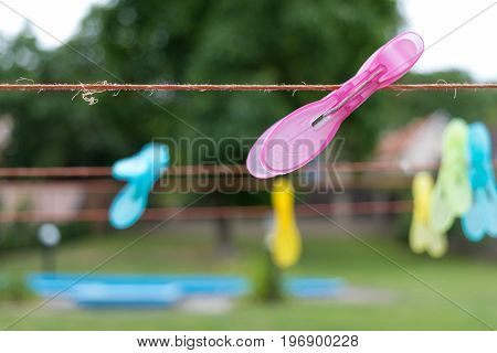 Clothespin clipped on a clothesline, garden with a pool in background