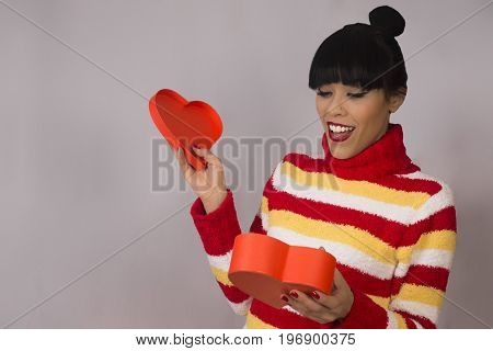 Surprised woman is opening orange gift box of heart shape.