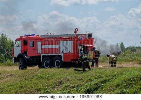 Fire truck and firemen in the forest