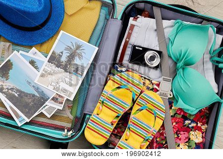 Essential beach things in suitcase. Close up of different accessories for summer tour.