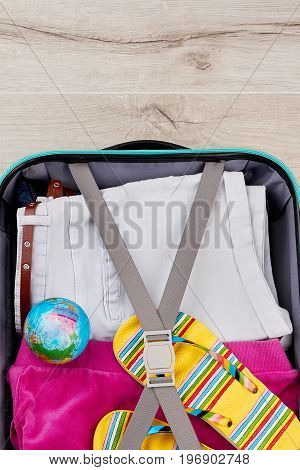 Vertical image of packed suitcase. Personal things in tourist bag, wooden background.
