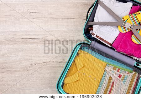 Suitcase with clothing, wooden surface. Luggage for summer trip, cropped image.