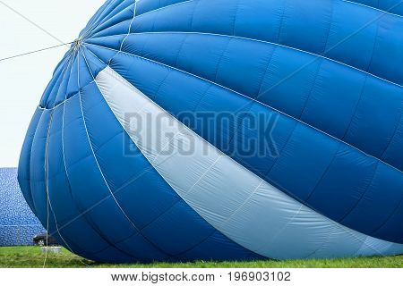 View from outside of a blue-white hot air balloon whan is inflated for flight next to a car
