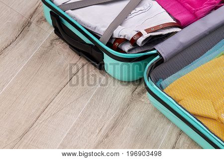 Modern suitcase with clothing. Packed tourister luggage, wooden surface.
