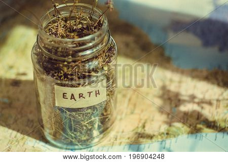 Planet Earth on the geographic map and dry medicinal herb in a glass jar, as a symbol of the environment and travels