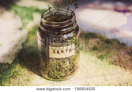 Earth on the geographic map and dry herb in a glass jar, as a symbol of the environment and world travels