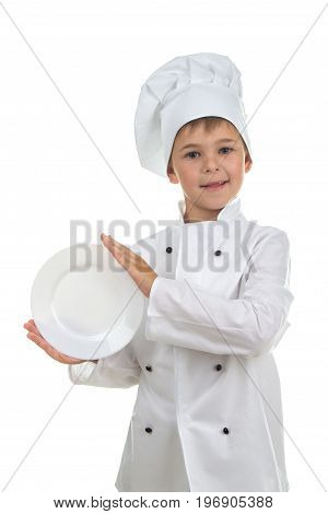 Funny kid wearing chef uniform holding plate in his hands on white background