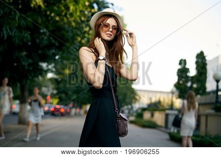 Young beautiful woman in sun glasses on the street in the city.