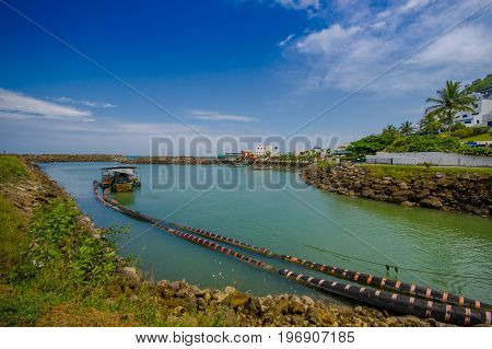 MANABI, ECUADOR - JUNE 4, 2012: Stagnant water with a water pumping machine at Same, Ecuador in a beautiful blue sky in a sunny day.