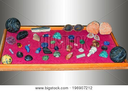 Various jewelery mineral stones or gemstones are placed on a tray with velvet.