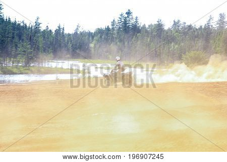 Man driving ATV quad in sandy terrain with high speed. Trail of dust behind the biker.