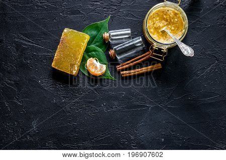 Making organic scrub. Scrub in glass jar, oranges, soap and oil on black stone background top view.
