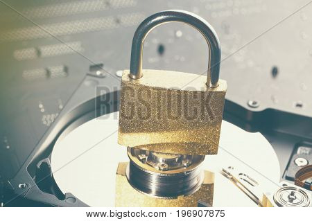 Hard disk drive plate with a padlock on it. Motherboard as a background. Internet data privacy information cyber crime security concept. Toned image