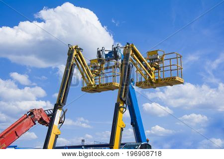Lift buckets boom in the blue sky with clouds
