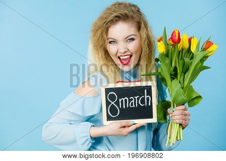 International women day. Beautiful woman blonde hair fashion make up holding red yellow tulips and frame board with message 8 march. On blue