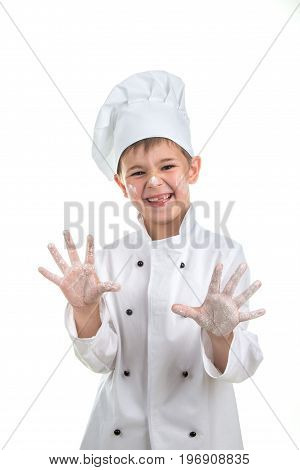 Cute playful little chef with flour on his hands.