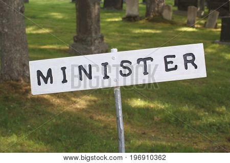 Minister parking sign with graveyard in background