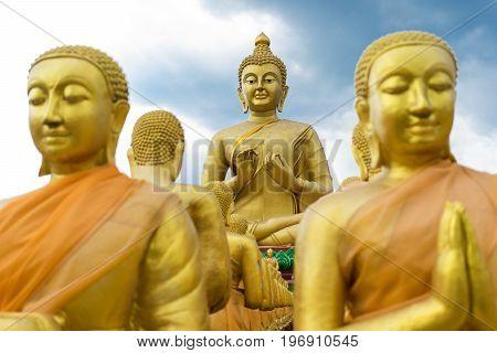Big Golden Buddha Statue surrounding by small Buddha Statues at Buddha Makabucha Memorial park Nakornnayok Thailand. Two small buddha were taken as foreground.