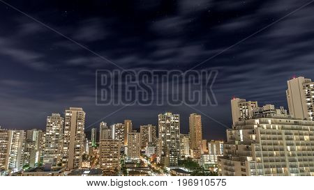 Watching the stars and clouds over the top of the buildings of downtown Waikiki Beach on Oahu Hawaii