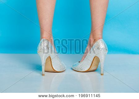 Female fashion. Silver high heels spiked fashionable shoes on legs. Studio shot against blue