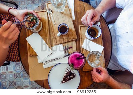 Couple of Man and woman on date having breakfast in the morning in cafe. Granola, chocolate cake, smoothie and hot coffee on the table. Flatlay, selective focus