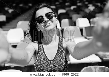 Close-up Portrait Of A Beautiful Fit Girl In Sunglasses Sitting In The Stadium. Black And White Phot