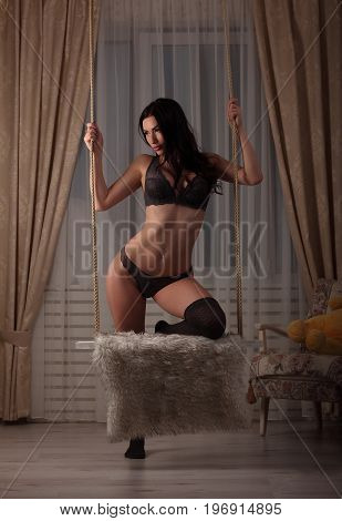 Sexy Brunette Slim Girl In Gray Lingerie Standing With One Leg On Swing