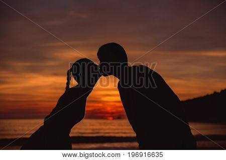 Romantic lovers kissing at twlilight with sunset in background