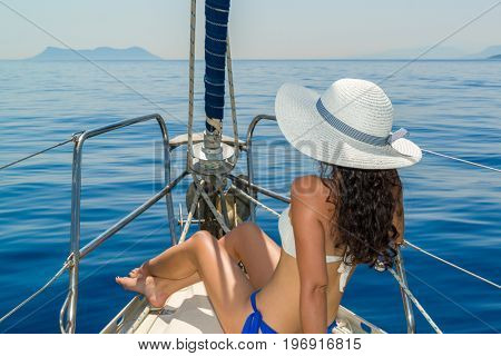 Woman relaxing on board of sailing yacht in Greece