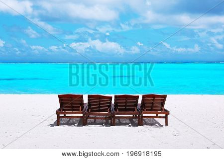 Wooden sun loungers on sea beach in summer day