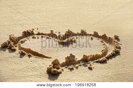 Drawing of heart on beach sand. Summer vacation concept