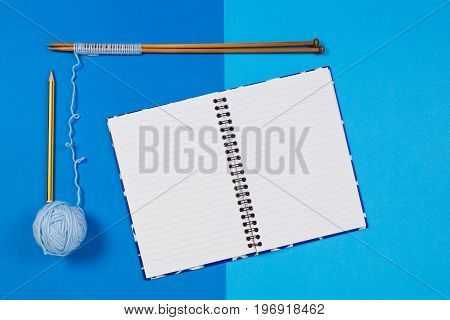 Knitting needles, blue yarn ball and open paper notebook on colorful blue background