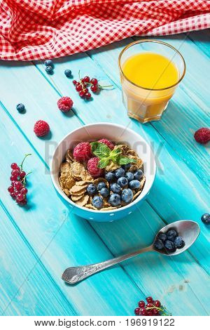 Multigrain wholewheat healthy cereals with fresh berry and a glass of juice for breakfast.