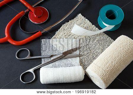 Medical Bandages With Scissors, Sticking Plaster And Medical Stethoscope On Black Background.