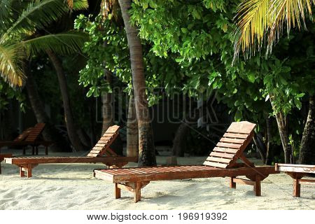 Tropical beach with sun loungers on summer day