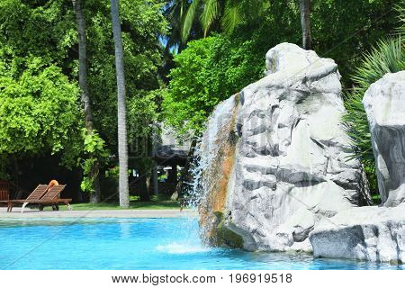 Artificial waterfall in beach hotel on summer day