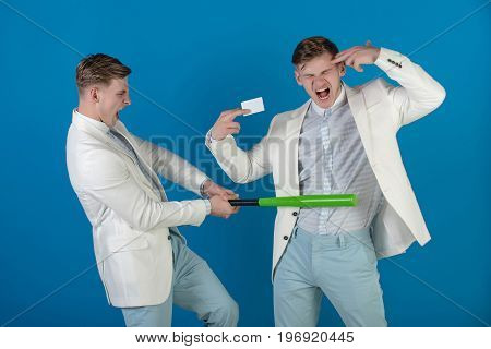 Managers shouting and fighting on blue background. Man showing finger gun with blank card. Businessman batting rival with baseball bat. By force or persuasion. Business negotiations concept.