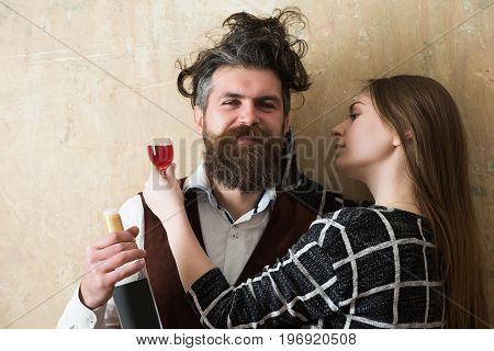 Couple in love hugging with glass and bottle of wine. Happy man or hipster with messy hair smiling with woman or girl on beige wall. Alcohol and convive. Unhealthy lifestyle. Bad habits