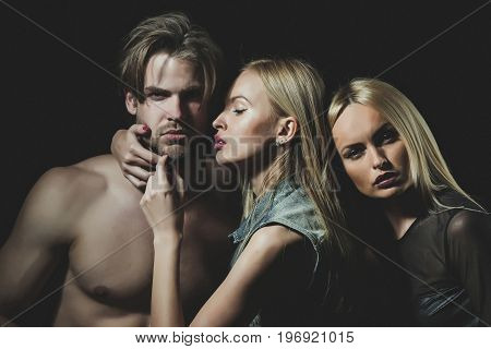 Relations of girls and guy. twins with sexy man. Love and romance. Man with muscular body with sexy women. Boyfriend and girlfriend on black