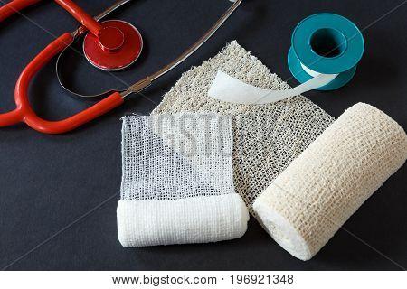 Medical Bandages With Adhesive Tape And Medical Stethoscope On Black Background.