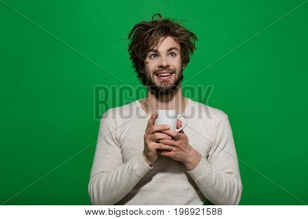 happy man with cup of tea or coffee has uncombed hair in underwear on green background morning refreshment and drink energy
