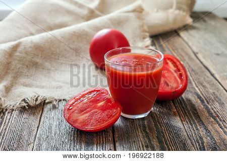 Tomato juice in a glass and slices of a tomato on a wooden table. Tomatoes and juice on wooden boards.