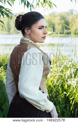 Woman in vintage clothes on the river bank